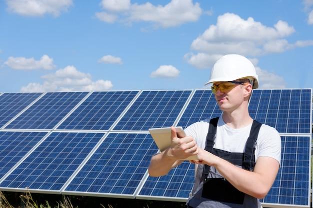 ソーラーパネルのフィールドの近くに立ってタブレットで入力する白いヘルメットと灰色の服を着たソーラーパネルエンジニア