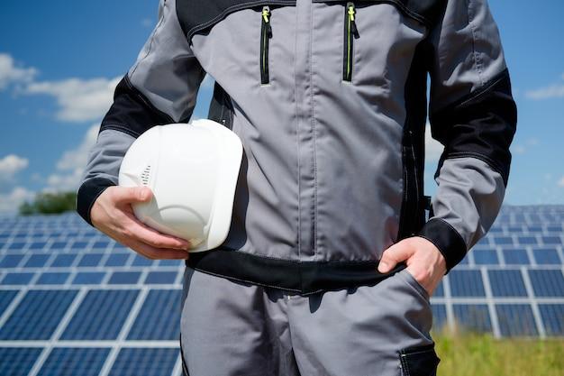 태양 전지 패널 엔지니어 또는 작업자 흰색 보호 헬멧을 들고
