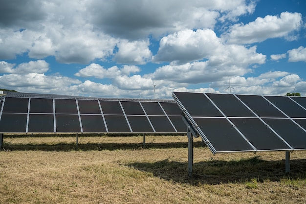 Solar panels in the grain field in the countryside under the cloudy sky