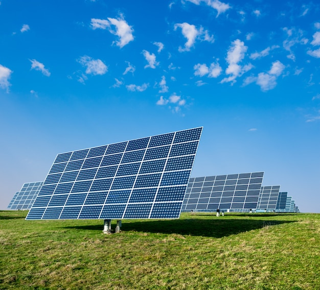 Solar panels on green field and blue sky