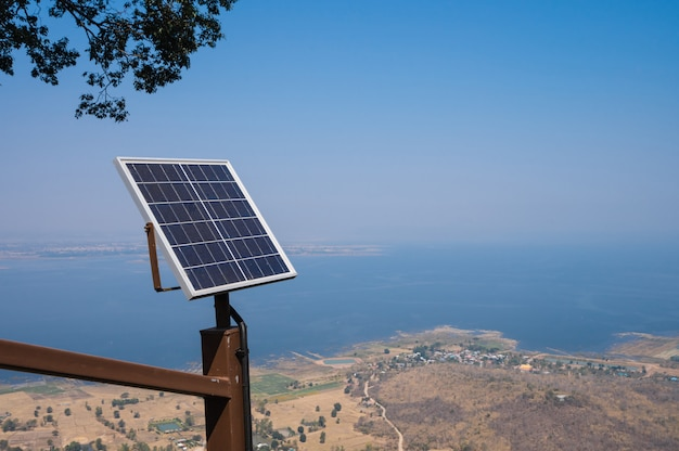 Solar panels on hill with dam view in misty air, produce electricity in a clean technology concept
