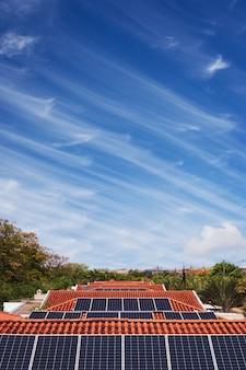 화창한 날과 흐린 날에 많은 집의 지붕에 태양 전지 패널 설치. 태양광 태양 에너지 개념 이미지입니다.