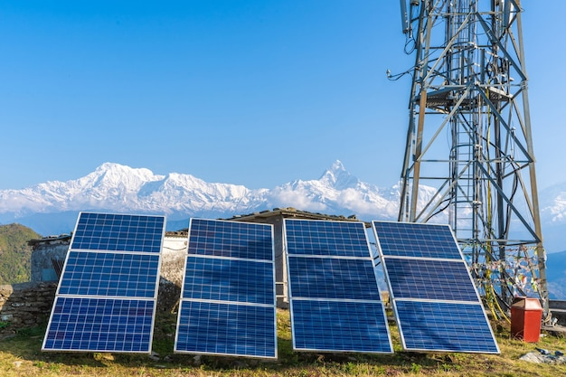 Панели солнечных батарей возле телекоммуникационной вышки в горном районе. заснеженные горные вершины на фоне. зеленые и экологически чистые источники энергии. запасное фото