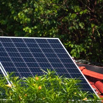 화창하고 흐린 날에 빨간 지붕 집에 태양 전지 패널. 태양광 태양 에너지 설치 개념 이미지입니다.