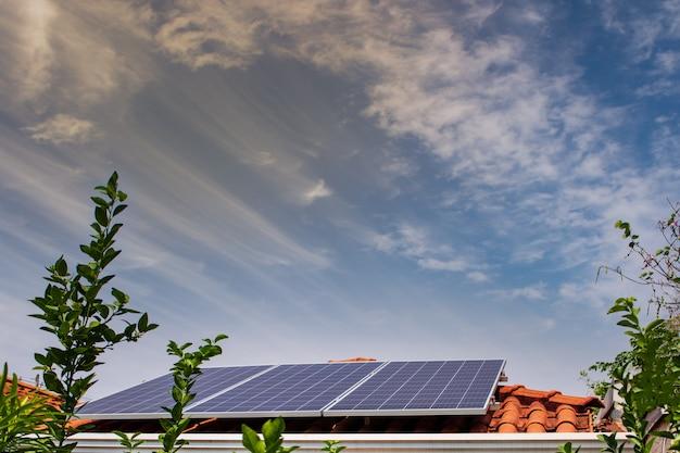 화창하고 흐린 날에 빨간 지붕에 태양 전지 패널. 태양광 설치 이미지.