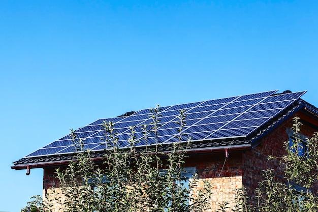 Солнечные батареи на крыше частного кирпичного дома на фоне голубого неба