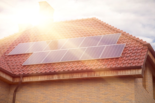 태양 아래 건물의 기와 지붕에 태양 전지 패널. 태양 전지 패널로 덮인 집 지붕. 대체 전력 소스 - 지속 가능한 자원 개념
