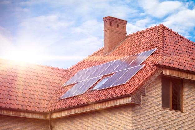 Солнечные батареи на черепичной крыше здания на солнце. крыша дома покрыта солнечными батареями. альтернативный источник электроэнергии - концепция устойчивых ресурсов