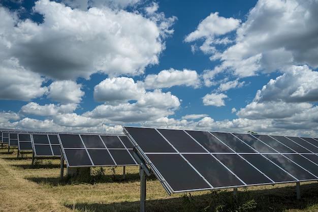 구름 가득한 하늘 아래 들판에서 재생 가능 에너지에 사용되는 태양 전지판