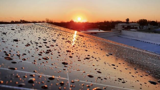 석양에 물 스프레이와 태양 전지 패널입니다.
