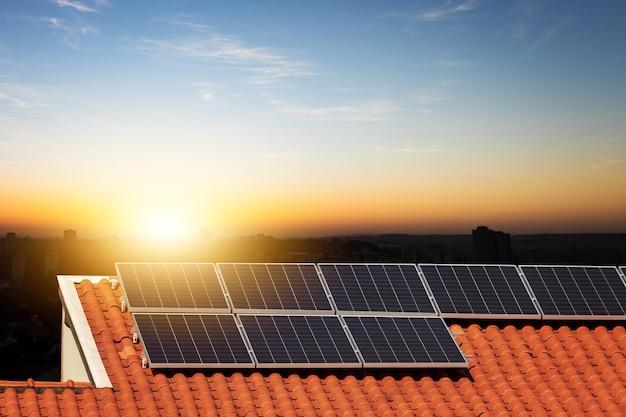 Солнечные фотоэлектрические панели на крыше на закате. современное изображение концепции дома или компании чистой энергии. место для текста.