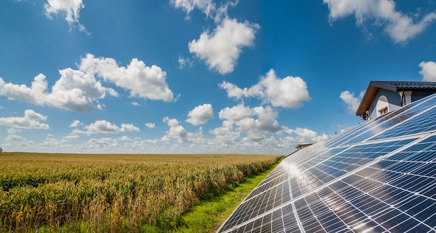 Solar power panels near a wheat field and cloudly sky