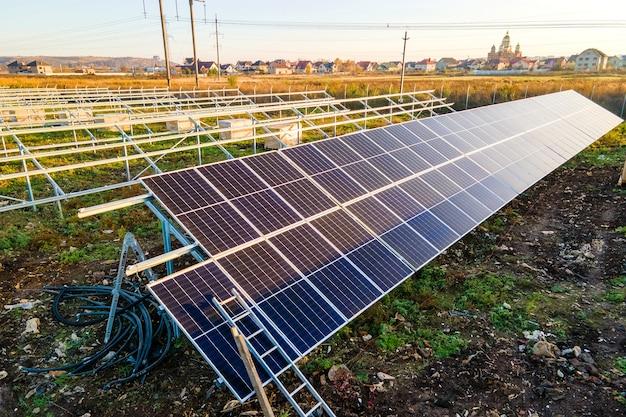 グリーンフィールドに建設中の太陽光発電所。クリーンな生態学的エネルギーを生み出すための電気パネルの組み立て。