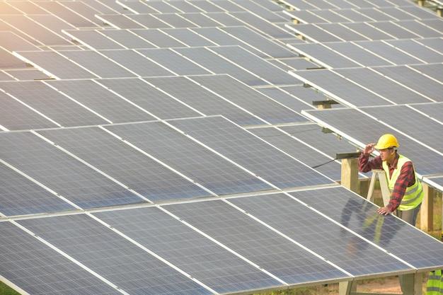 Солнечная электростанция, солнечные панели с техником, электротехническое производство будущего, азиатские инженеры