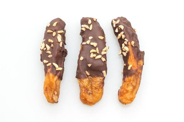 Вяленый на солнце банан в шоколадной глазури или шоколад в банане, изолированные на белом фоне