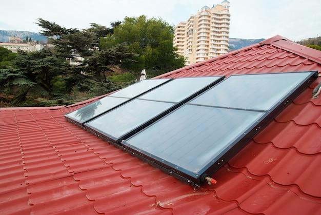赤い家の屋根にある太陽熱温水暖房システム(ジェリオシステム)。