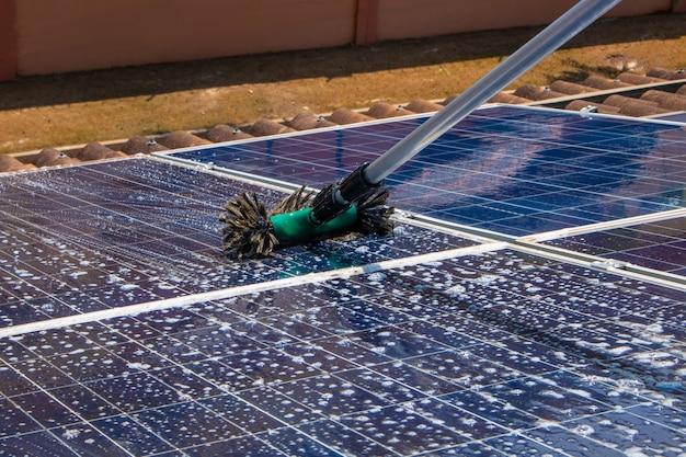솔과 물로 태양광 패널을 청소하는 태양광 노동자. 태양광 청소.