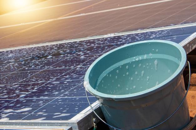 Солнечный работник чистит фотоэлектрические панели щеткой и водой. фотоэлектрическая очистка.