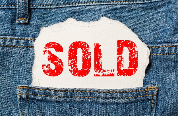 Sold on white paper in the pocket of blue denim jeans