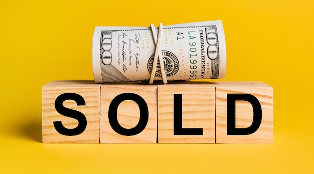 Sold with money on a yellow background. the concept of business, finance, credit, income, savings, investments, exchange, tax