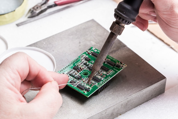 Soldering chips iron over in female hands