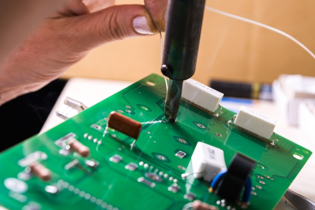 Soldering iron over the chip in female hands