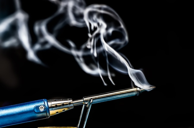 Soldering iron with smoke on a black background. electrical, electronics