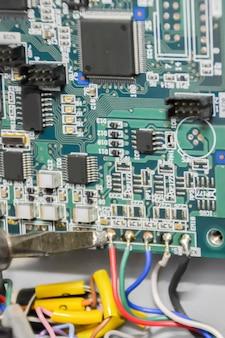 납땜. 매크로 사진. 플레이트에 텐서 센서를 납땜합니다. 마이크로 전자 공학 및 기술 개념입니다. 기술자가 전자 부품을 수리하고 있습니다.