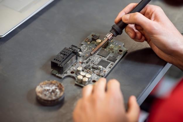 Микросхема пайки. мужские опытные руки с частями паяльника горячего паяльника на микросхеме на рабочем столе.