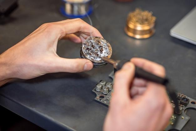 Процесс пайки. осторожные руки с горячим паяльником возле круглой коробки касаются припоя и микросхемы, лежащей на столе