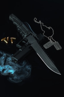 Solders combat knife and gun on black background