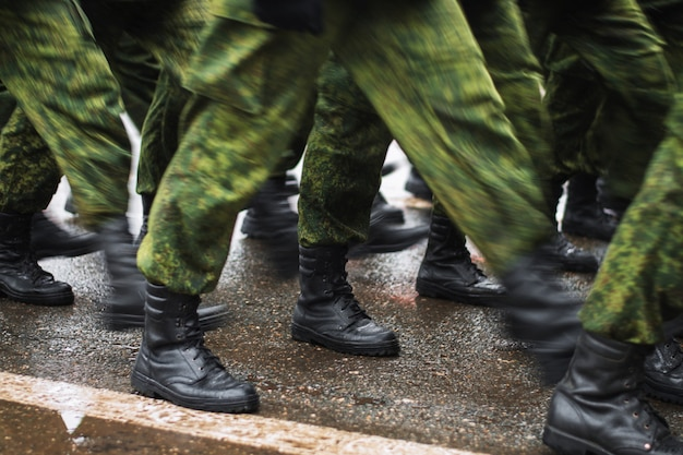 Soldier boots walking on wet asphalt during the parade of memory. the military marching down the street. many shoes and camouflage clothing. motion lubrication