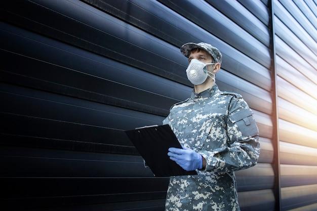 Soldato in uniforme mimetica che indossa guanti protettivi e maschera in una missione contro il virus corona