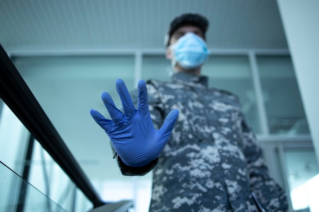 Soldier in camouflage uniform wearing protective gloves and mask showing stop sign at hospital entrance
