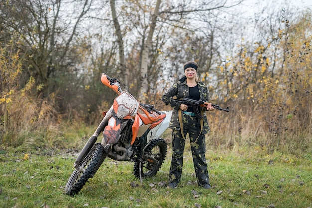 Soldier in camouflage with rifle and dirty motorcycle