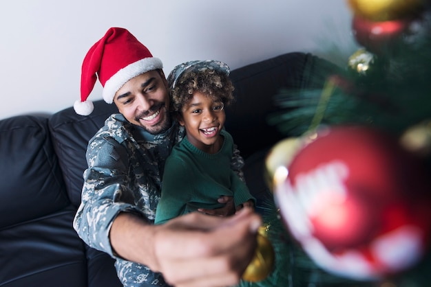 Soldier decorating christmas tree with his daughter