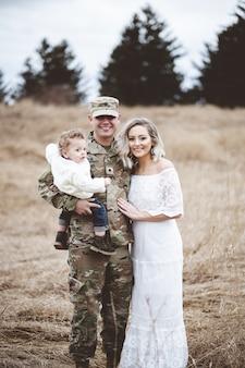 彼の息子と美しい若い妻を保持している兵士の父