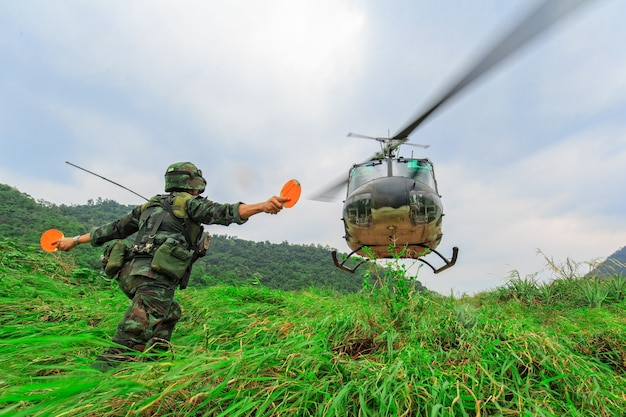 兵士が山にヘリコプターの着陸信号を出す