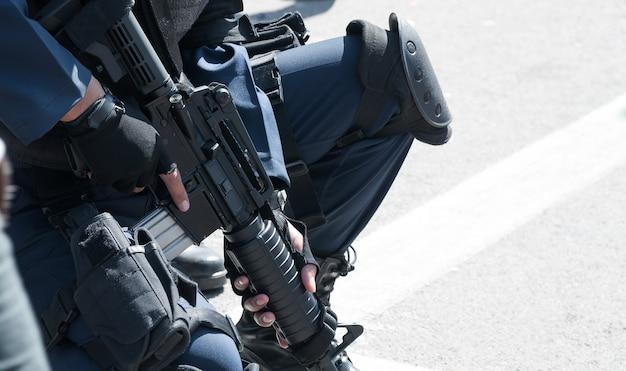 Солдат держит автомат с автоматом. подготовка к боевым действиям. солдат, одетый в защитное снаряжение