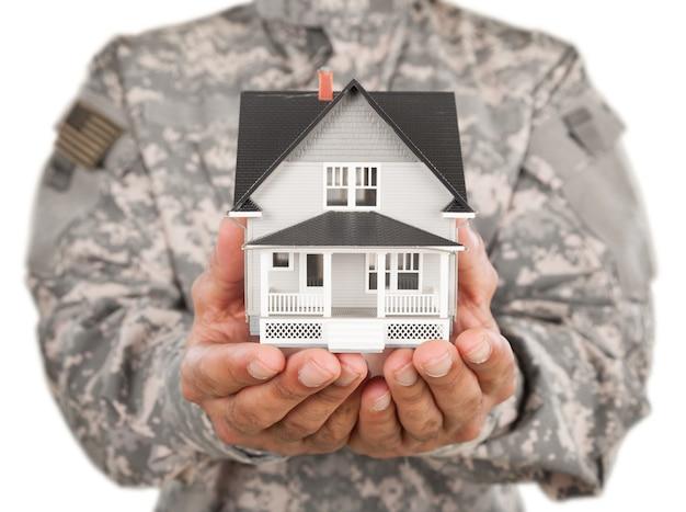 집의 모형을 들고 있는 군인