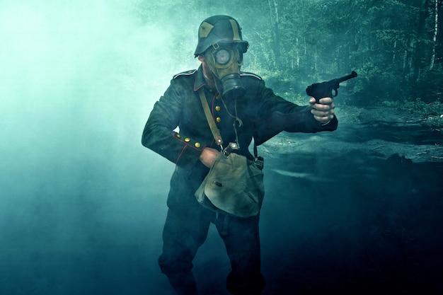 Солдат в противогазе целится из пистолета.
