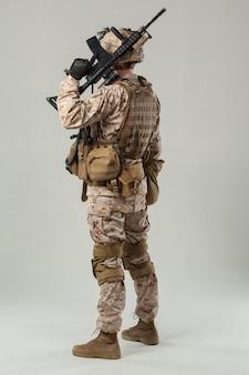 Солдат в камуфляже держит винтовку