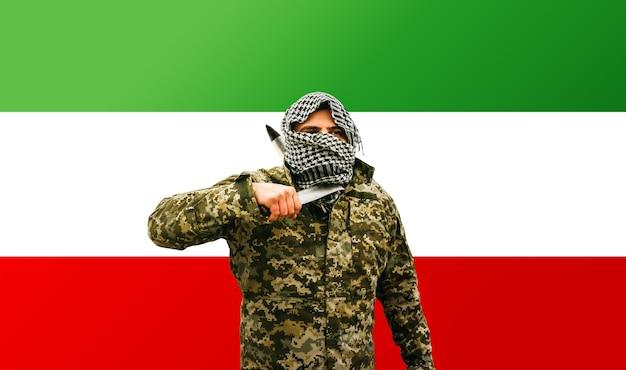 イランの旗の背景にカモフラージュの制服を着た兵士。戦争の概念。対立の問題。