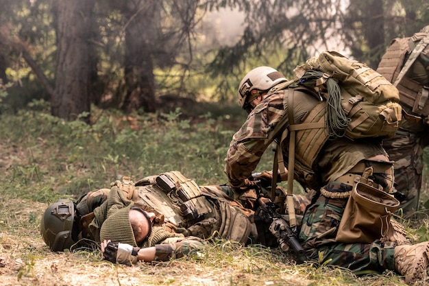 헬멧을 쓴 군인은 죽은 동료 옆에 무릎을 꿇고 전장에서 총을 쏘고 숲 속의 안개 프리미엄 사진
