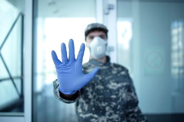 病院の入り口の前に立って、停止ジェスチャーのサインを示しているミリタリーカモフラージュの制服を着た兵士