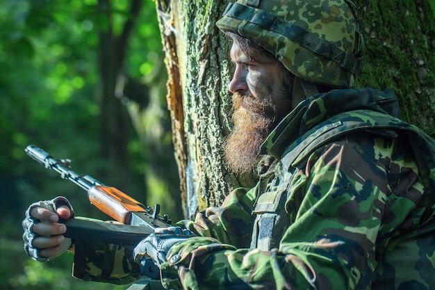 軍服と屋外の木と緑の森にライフルとヘルメットの兵士