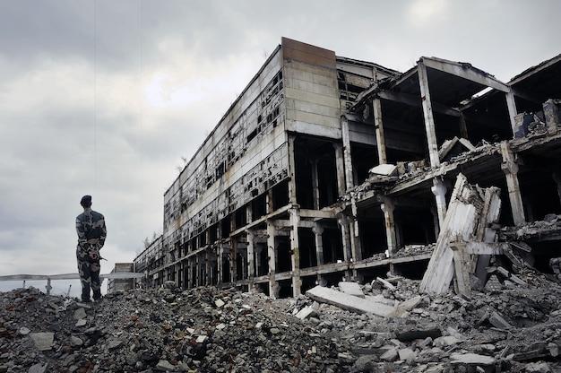 군복을 입은 군인이 파괴된 집의 폐허 위에 서 있습니다. 행성의 핫스팟. 테러와의 전쟁의 개념입니다.