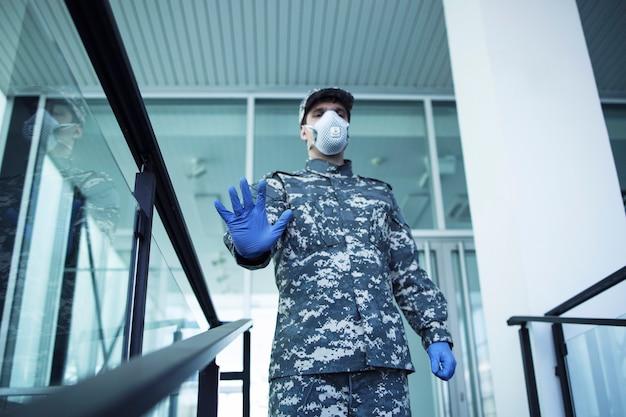 Солдат в военной форме с резиновыми перчатками и маской для лица охраняет двери больницы и жестикулирует со знаком остановки
