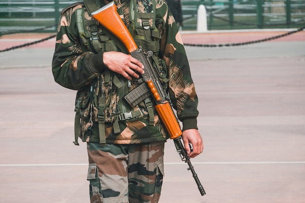 퍼레이드 제복을 입은 군인이 인도 델리에서 손에 총을 들고 인도 게이트를 지키고 있습니다. 인디아 게이트는 1921년 edwin lutyens에 의해 세워졌습니다.