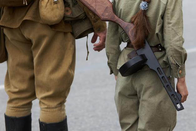 붉은 군대의 형태로 군인과 기관총을 가진 소녀가 순서대로 서있다.